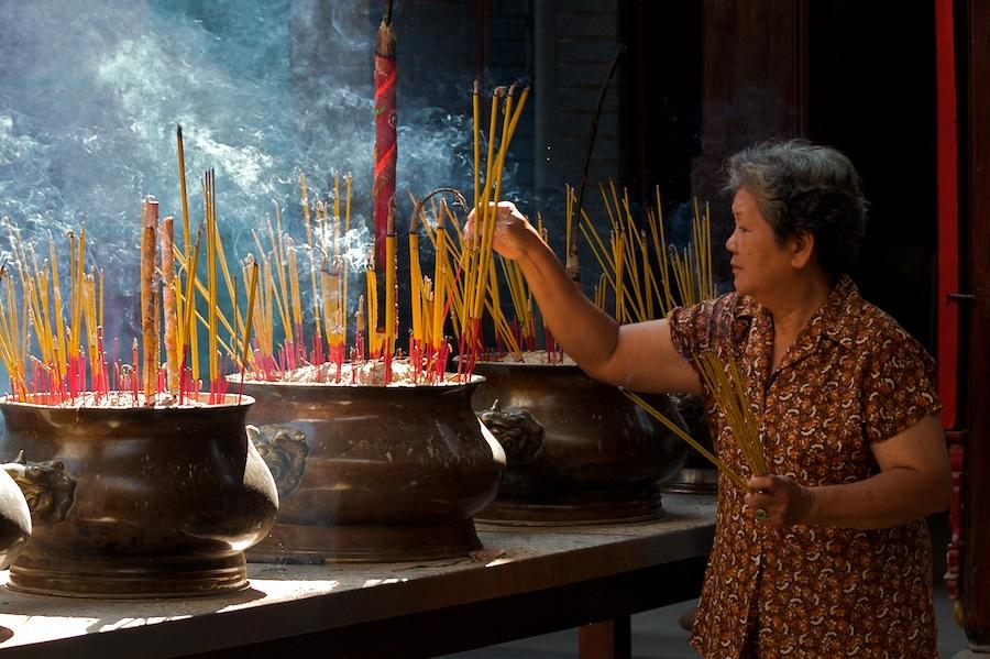Eine Frau opfert in der Thien-Hau-Pagode