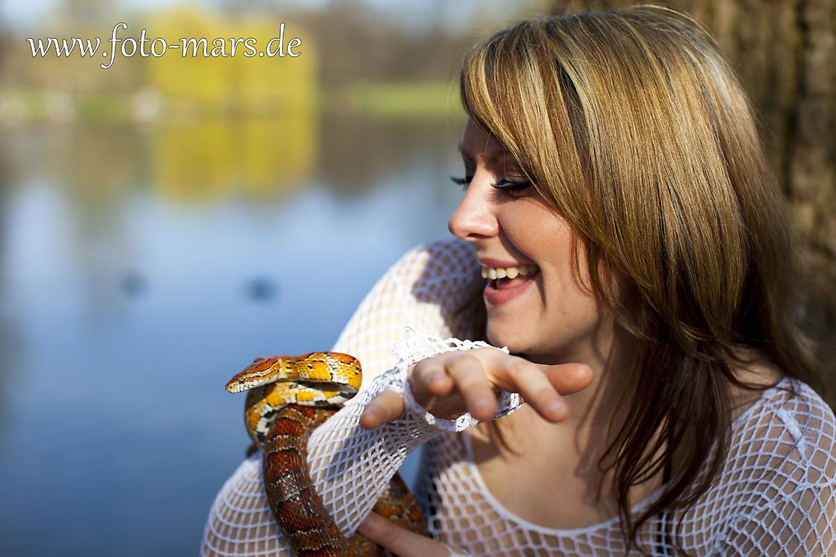 Eine glückliche Frau mit hübscheSchlange.