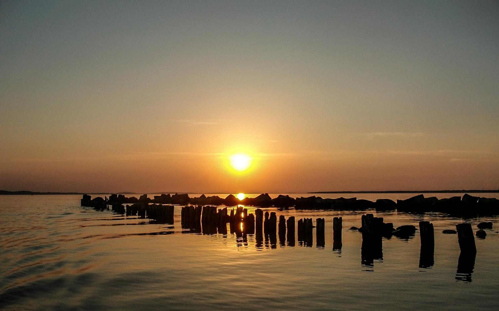 eine Hafeneinfahrt am großen Jasmunder Bodden mit beginnenden Sonnenuntergang