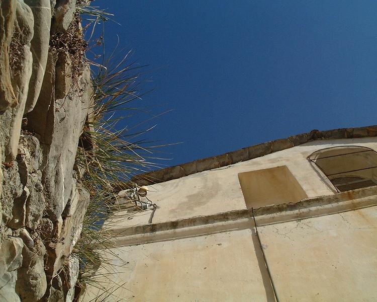 Eine italienische Kapelle mit angrenzender Steinmauer im Winter