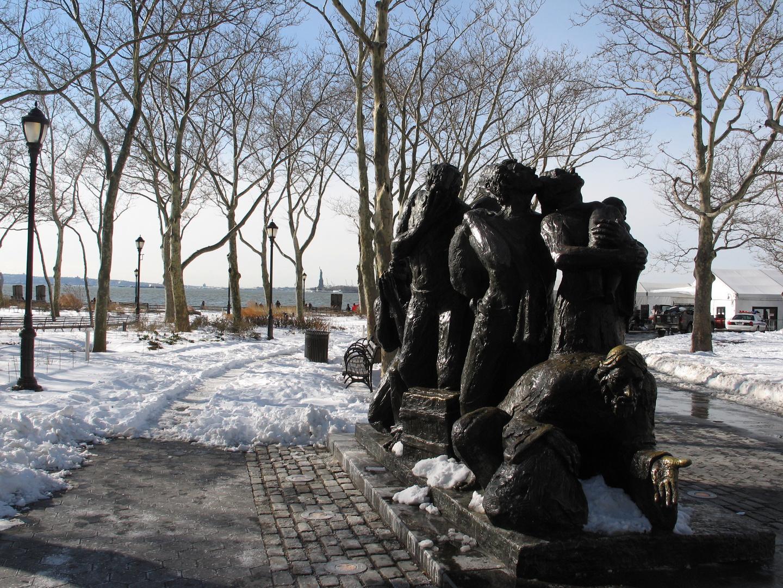 Einwanderer-Denkmal in New York; im Hintergrund die Freiheitsstatue (Weihnachten 2009)
