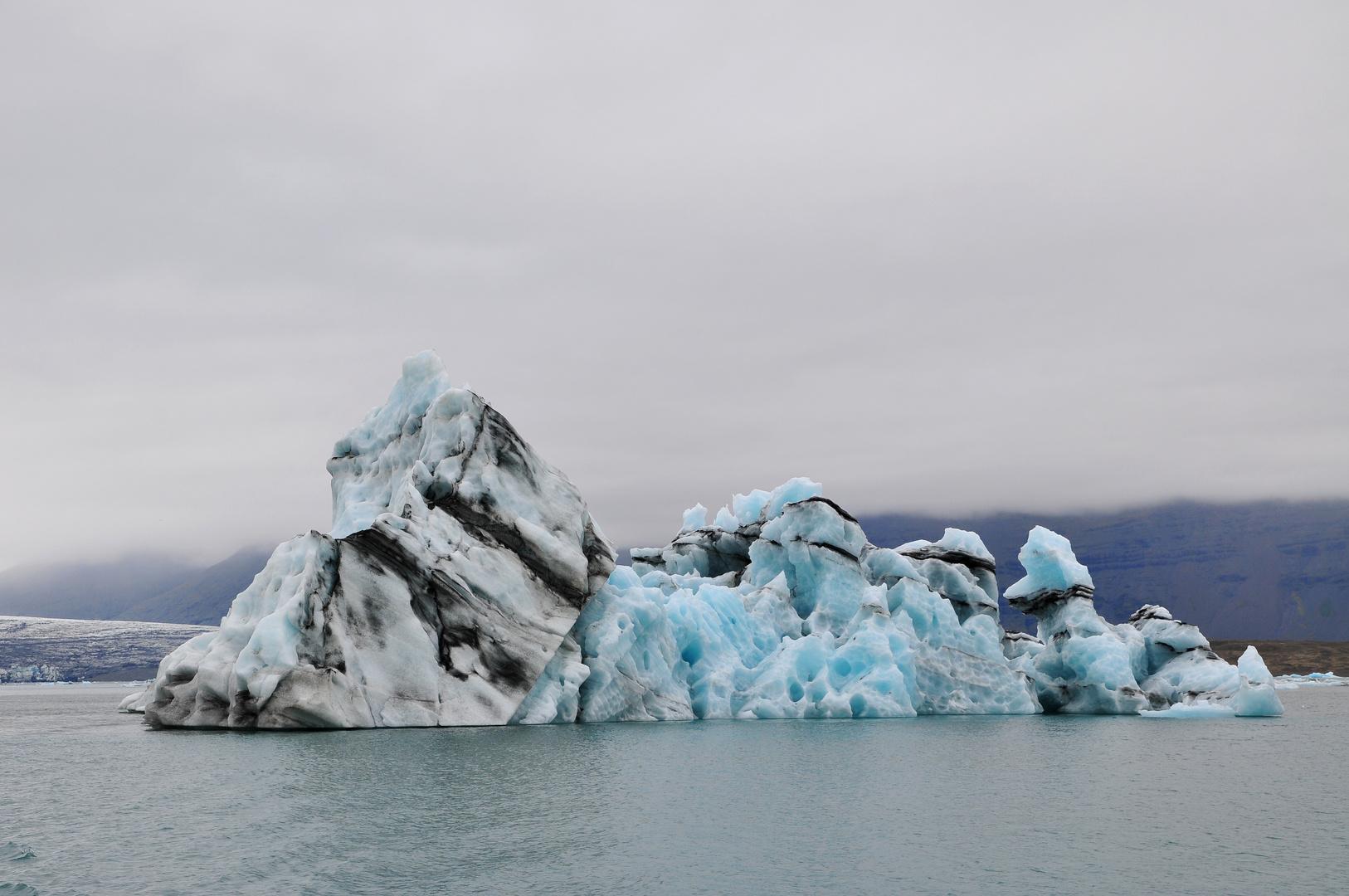 Eisberg mit Lavaascheschichten in der Gletscherlagune Jökulsárlón