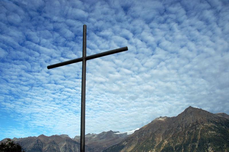 Eisen-Kreuz vor Wolkenhimmel über der Adula-Gruppe