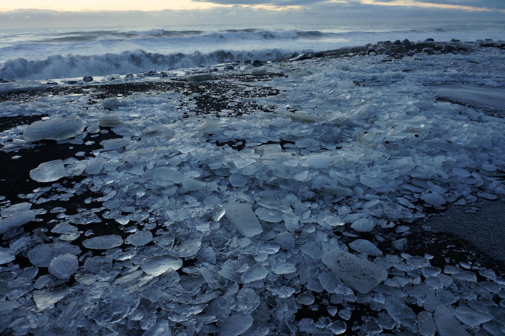 Eisperlen auf schwarzem Sand