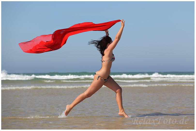 """""""Endlich Urlaub"""" - Junge Frau mit wehendem rotem Tuch läuft am Meeresstrand entlang"""