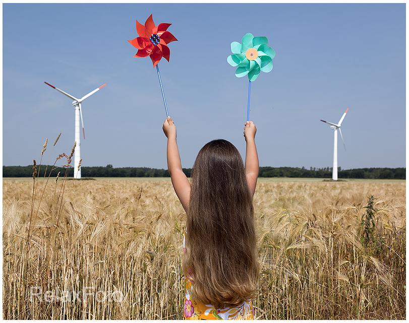 """""""Energiewende"""" - Kleines langhaariges Mädchen mit Windspiel vor Windrädern"""