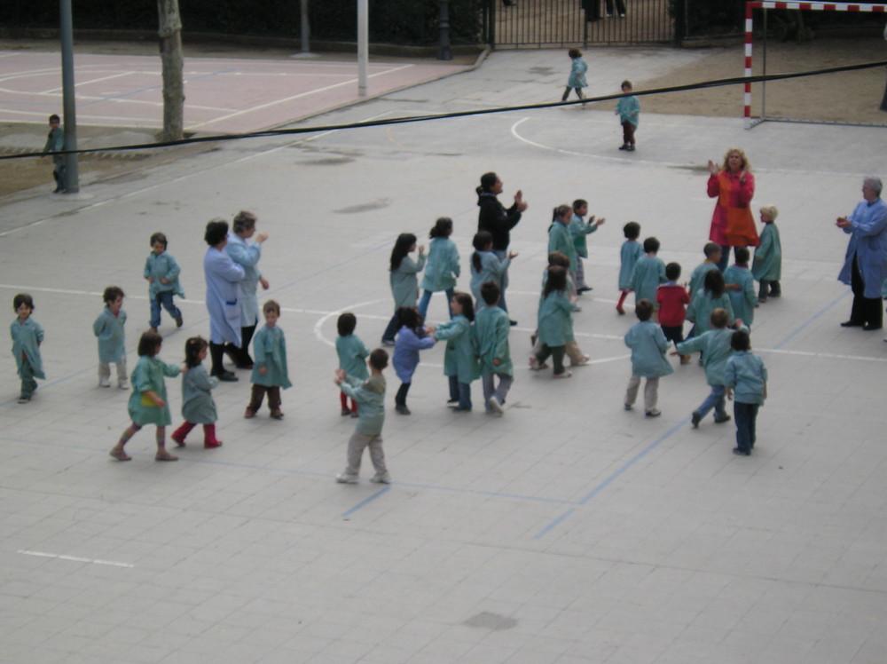 Enfants Barcelonais en blouses dans leur cours de récréation