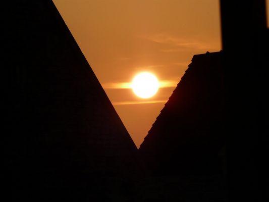 Entre deux pans de toit... Un coucher de soleil flamboie ... :)