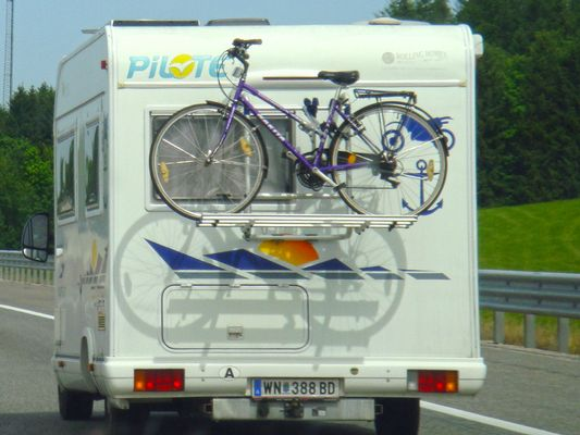 Fahrrad und Fahrradschatten auf Rückseite eines Wohnwagens auf der Autobahn
