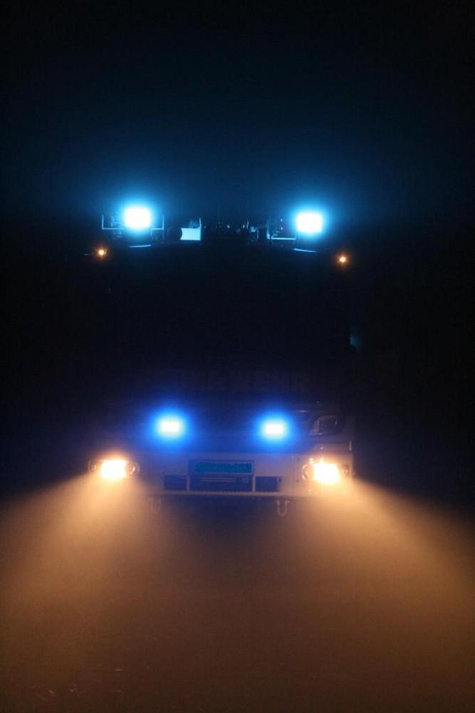 Feuerwehr HLF20/16 bei Nacht im Nebel mit Blaulicht