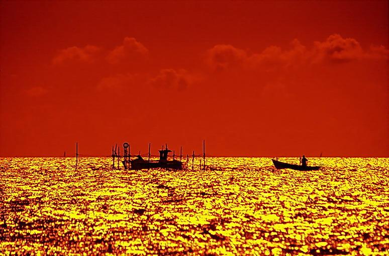 Fischer holen bei Sonnenuntergang die Netze ein...