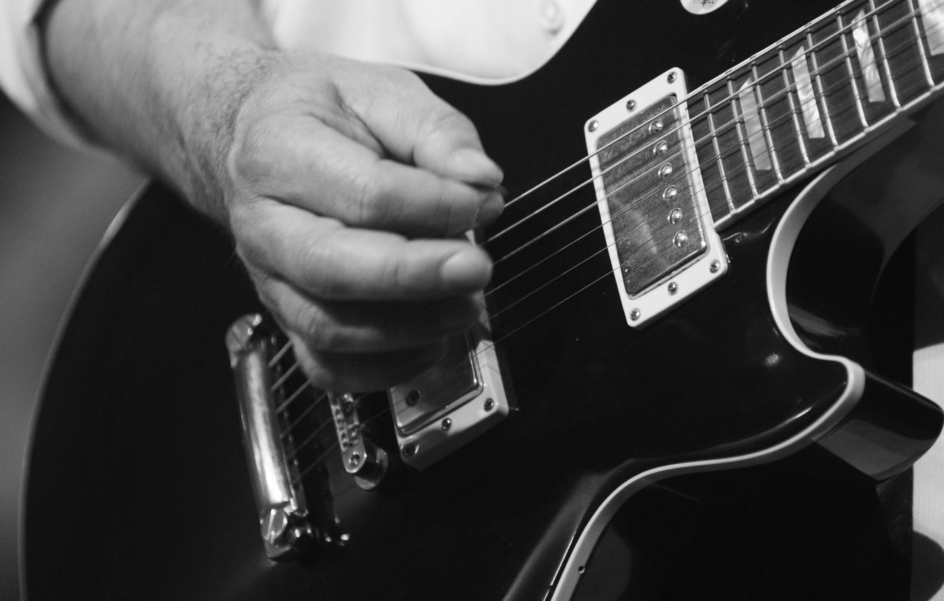 Flinke Finger huschen über die Saiten der E-Gitarre...