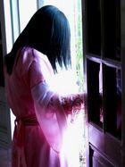 Frau in Licht und Schatten umhüllt von zarter Seide
