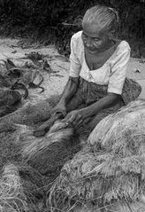 Frau klopft Kokosfasern am Strand von Talala (Sri Lanka)