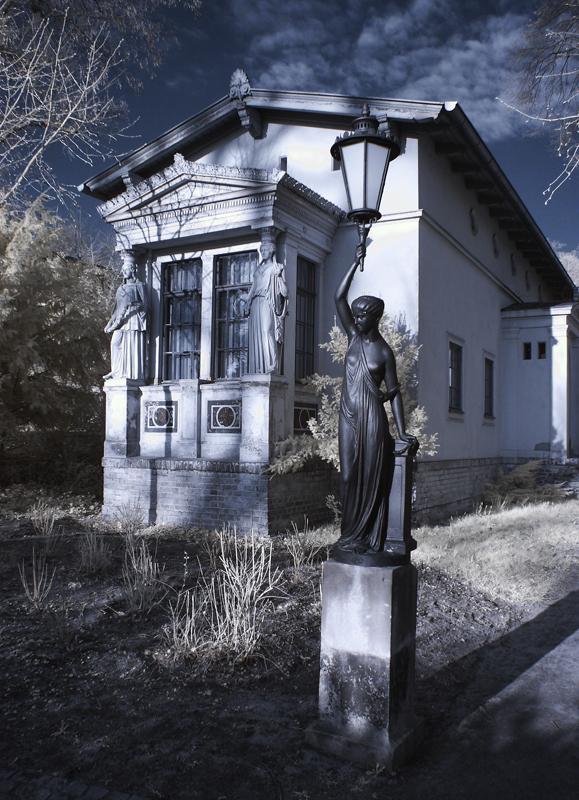 Frau mit Lampe vor Haus