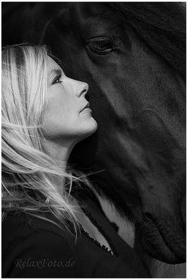 """""""Freundschaft zwischen Mensch und Tier"""" - Porträt einer blonden Frau vor schwarzem Pferdekopf"""