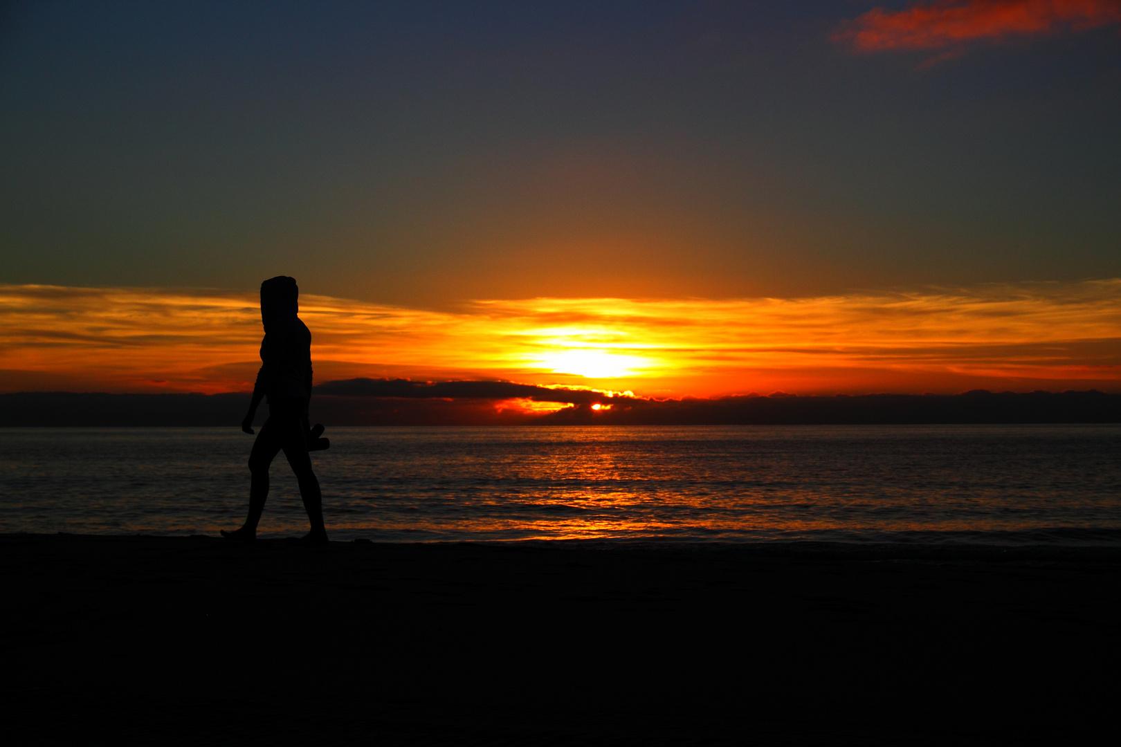 Früh am Morgen am Strand (Sonnenaufgang mit Jogger)