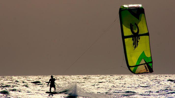 ganz lässig gleitet der Kitesurfer über die Wellen der Playa de Sotavento