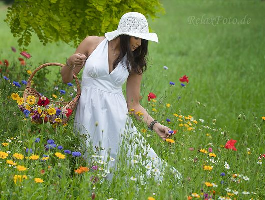 """""""Garten Eden"""" - Junge Frau (Inderin) in weißem Sommerkleid pflückt Blumen in Wildblumenwiese"""