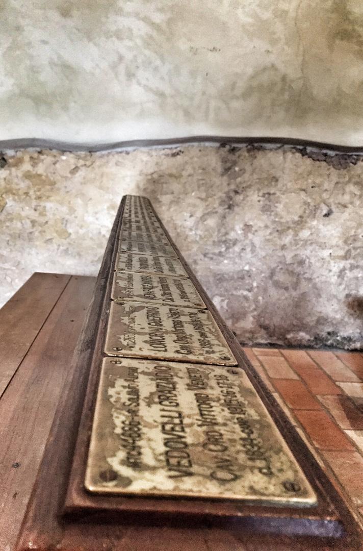 Gebetsbank mit Namenstafeln in einer kleinen Kapelle in Italien