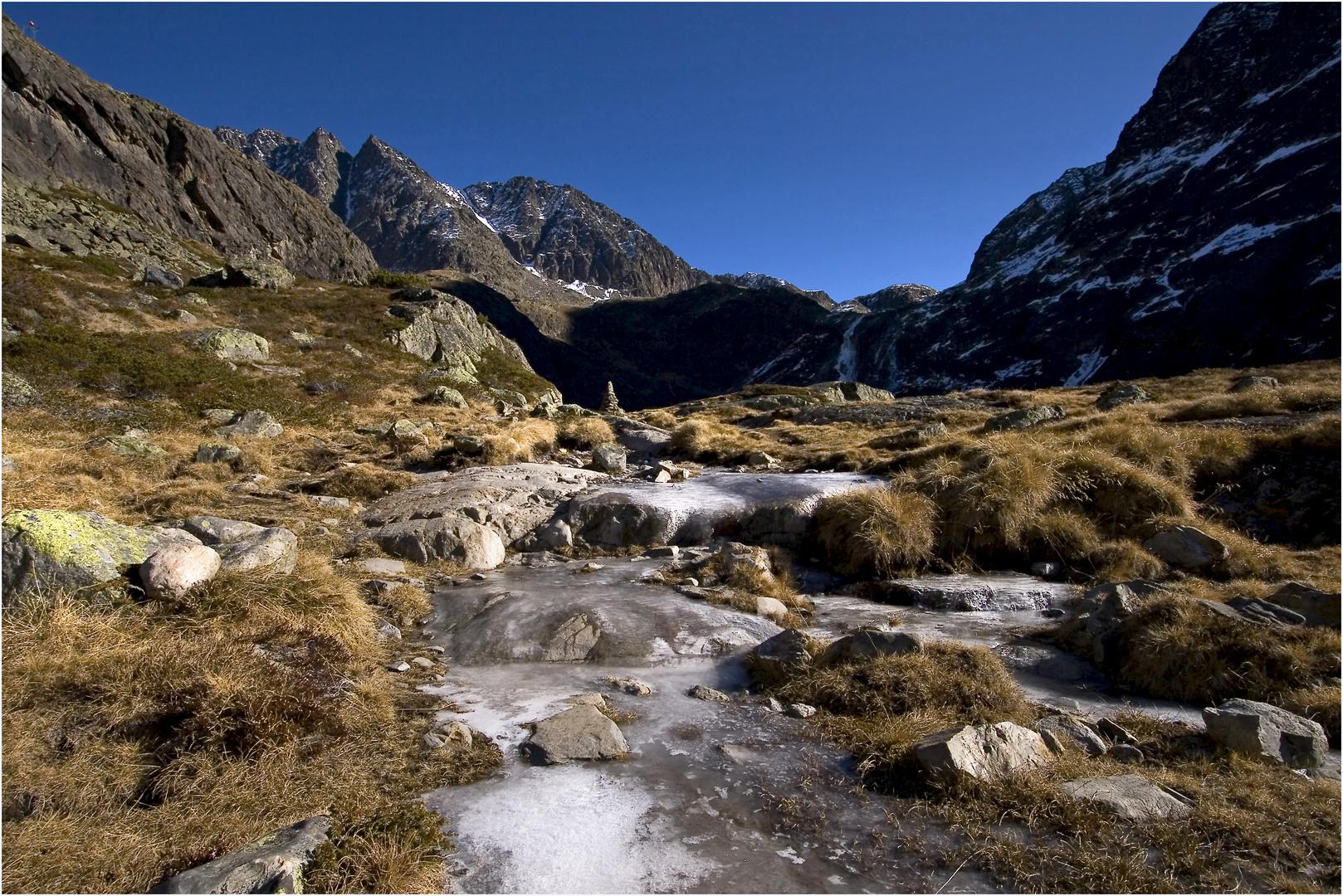 gefrorenes Bachl und ein Steinmandl weißt den Weg