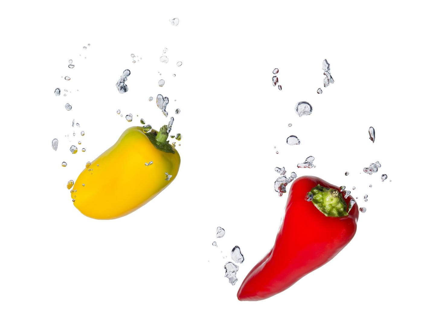 Gelbe und rote Paprika im Wasser mit Luftblasen