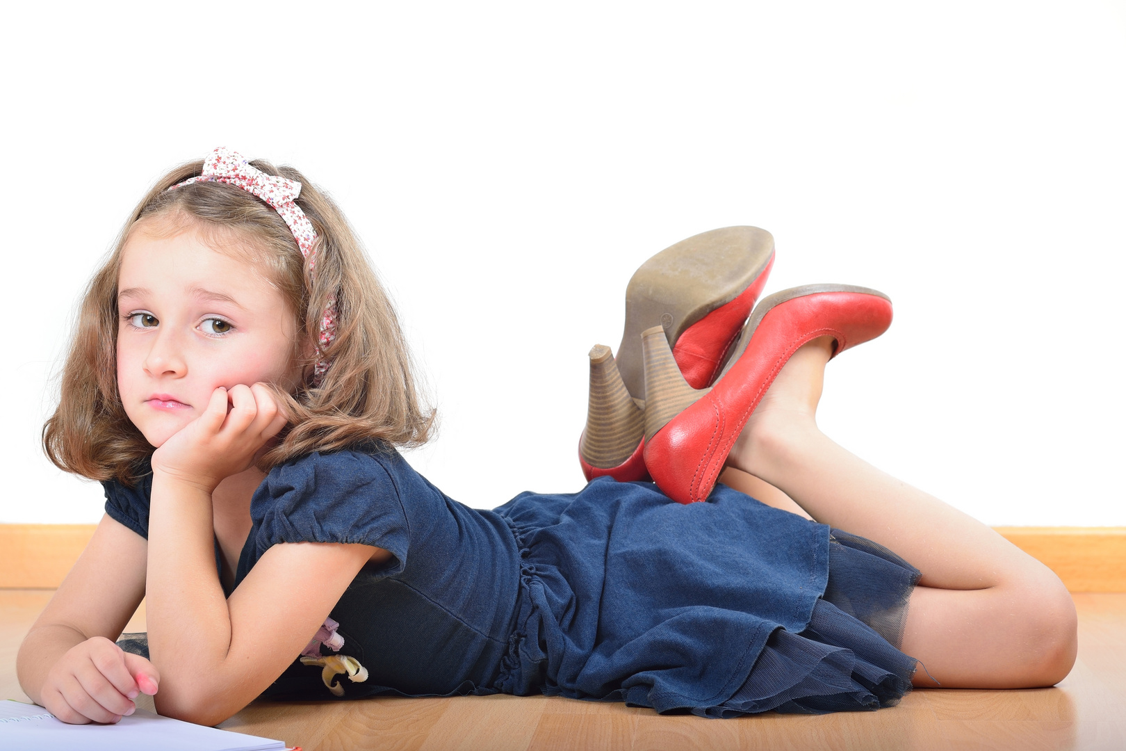 Girl wearing mother's shoes is reading and posing