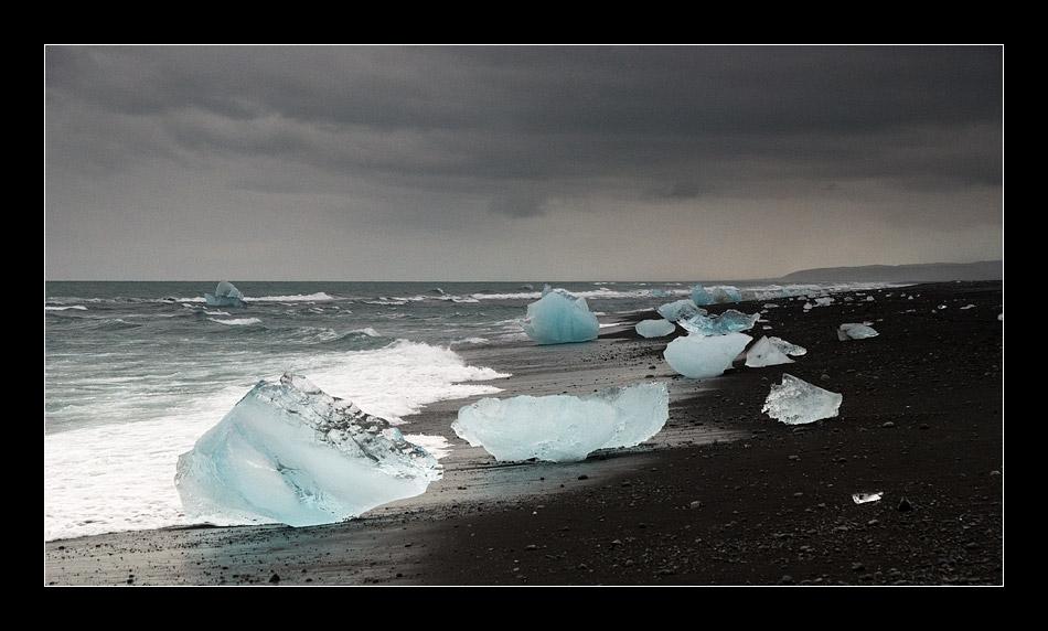 Gletscherbrocken auf schwarzem Lavasand
