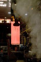 Glühendes Stahlrohr wird zur Weiterverarbeitung transportiert