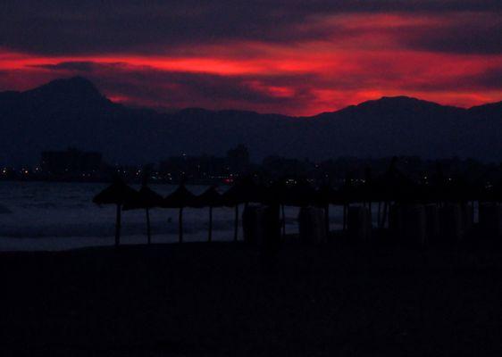 Glutrot verbrennen die Wolken am Abendhimmel.