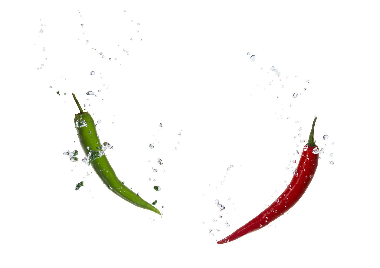 Grüne und rote Chili im Wasser mit Luftblasen