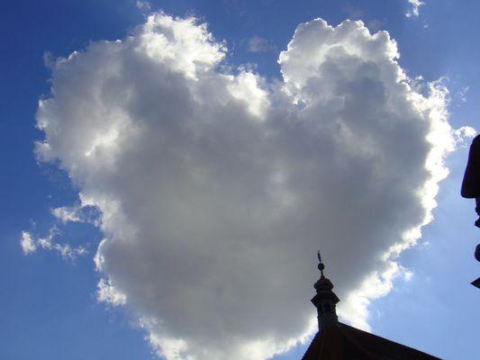 Herzförmige Wolke neben einem Kirchturm
