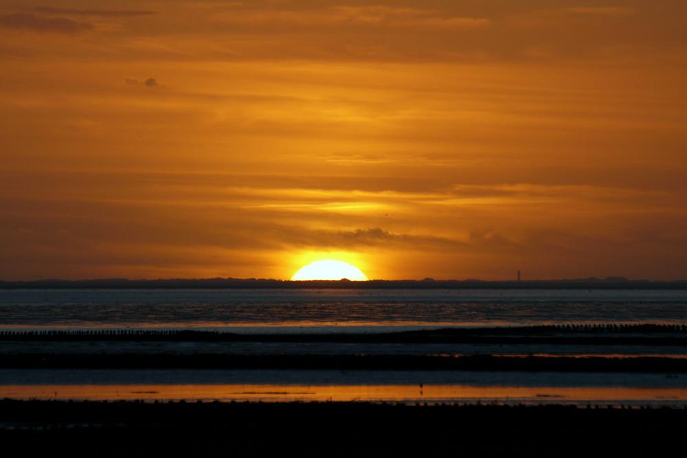 Hinter Sylt versinkt die Sonne