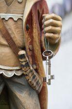 Holzfigur hält Schlüssel