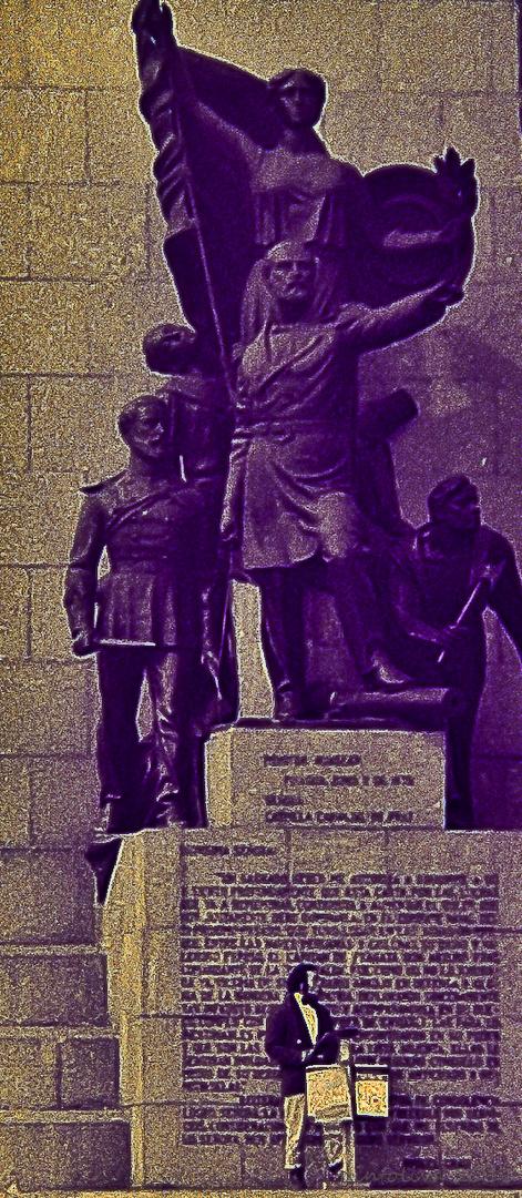 Hombre orquesta al pié de monumento a Prat.