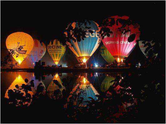 hot air balloon night glow ,vu à travers les arbres
