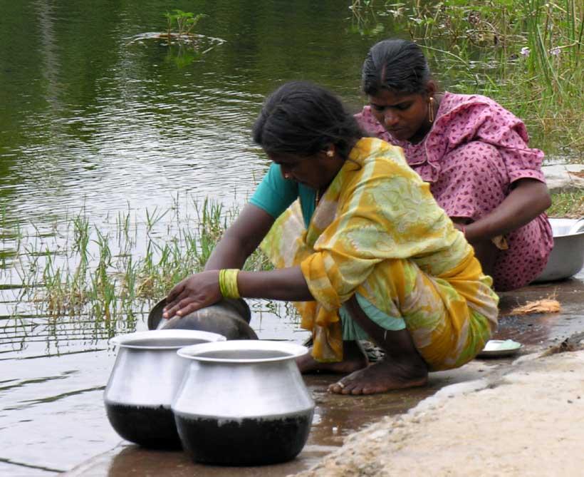 Indische Frauen beim Geschirrspuelen