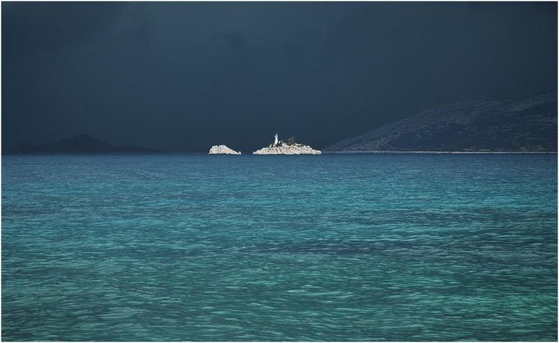 Insel mit Leuchtturm vor Gewitter