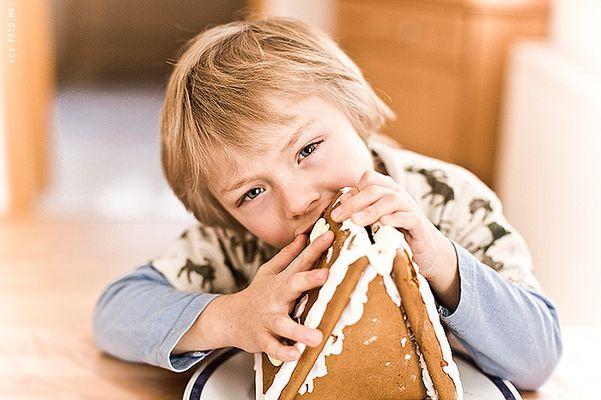 Junge beißt in Lebkuchenhaus