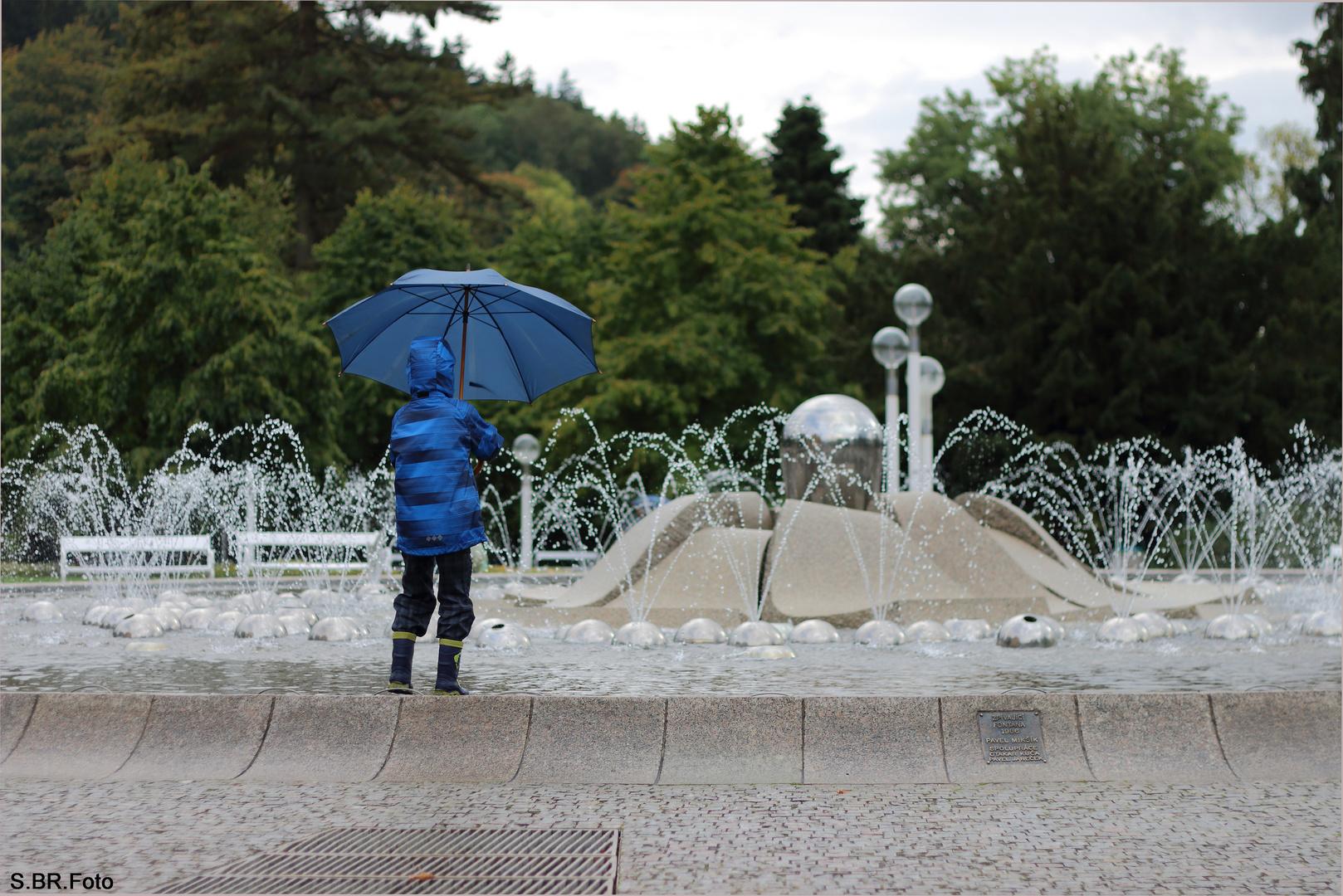 Junge spielt am Brunnen