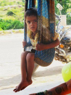 kind in sari-schaukel