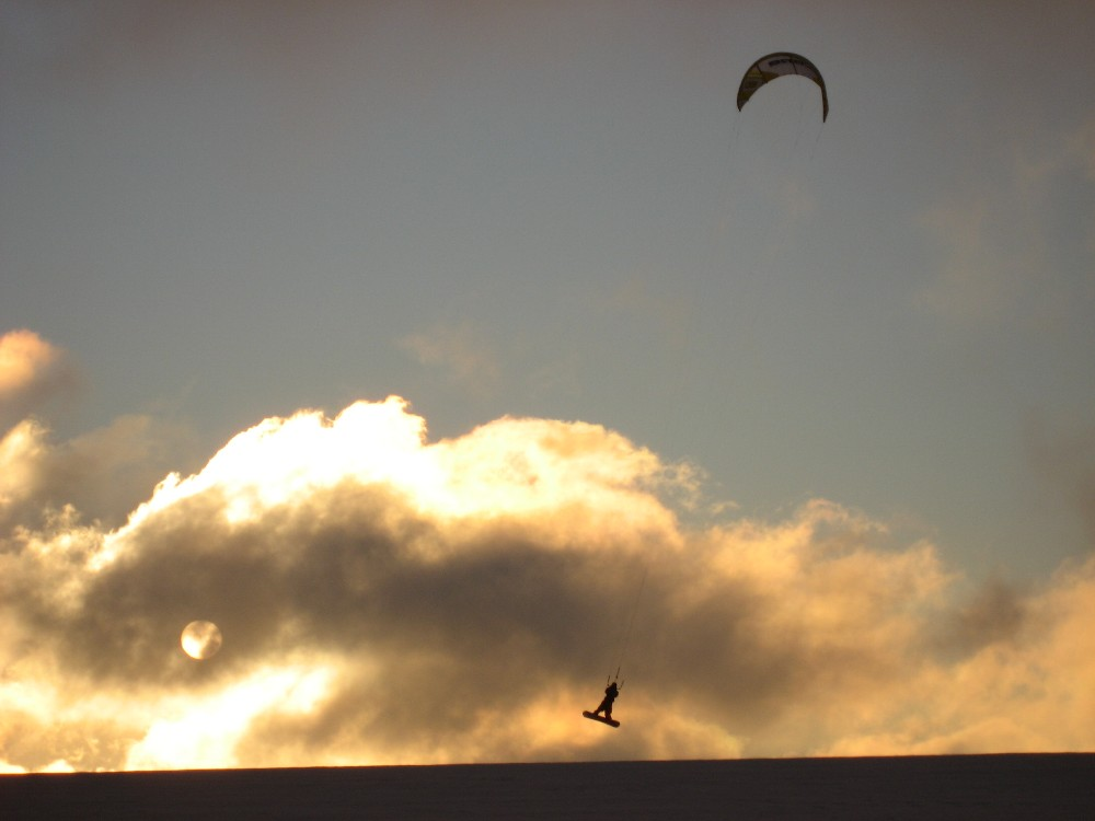 Kite snowboarden in der Abenddämmerung