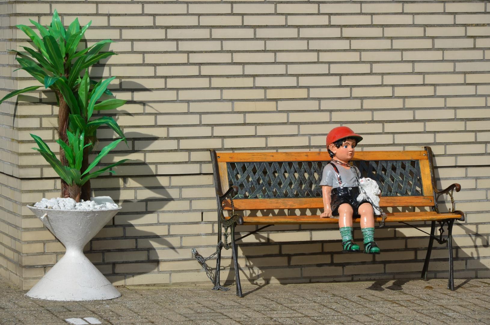 kleiner Junge sitzt auf der Bank