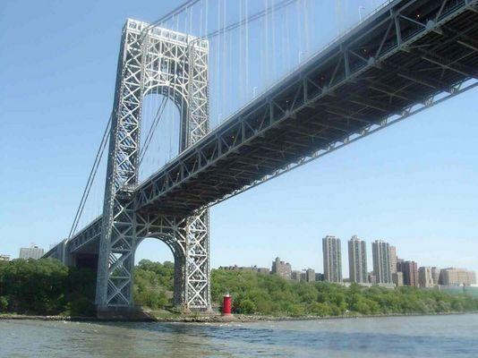 Kleiner Leuchtturm unter großer grauer Brücke