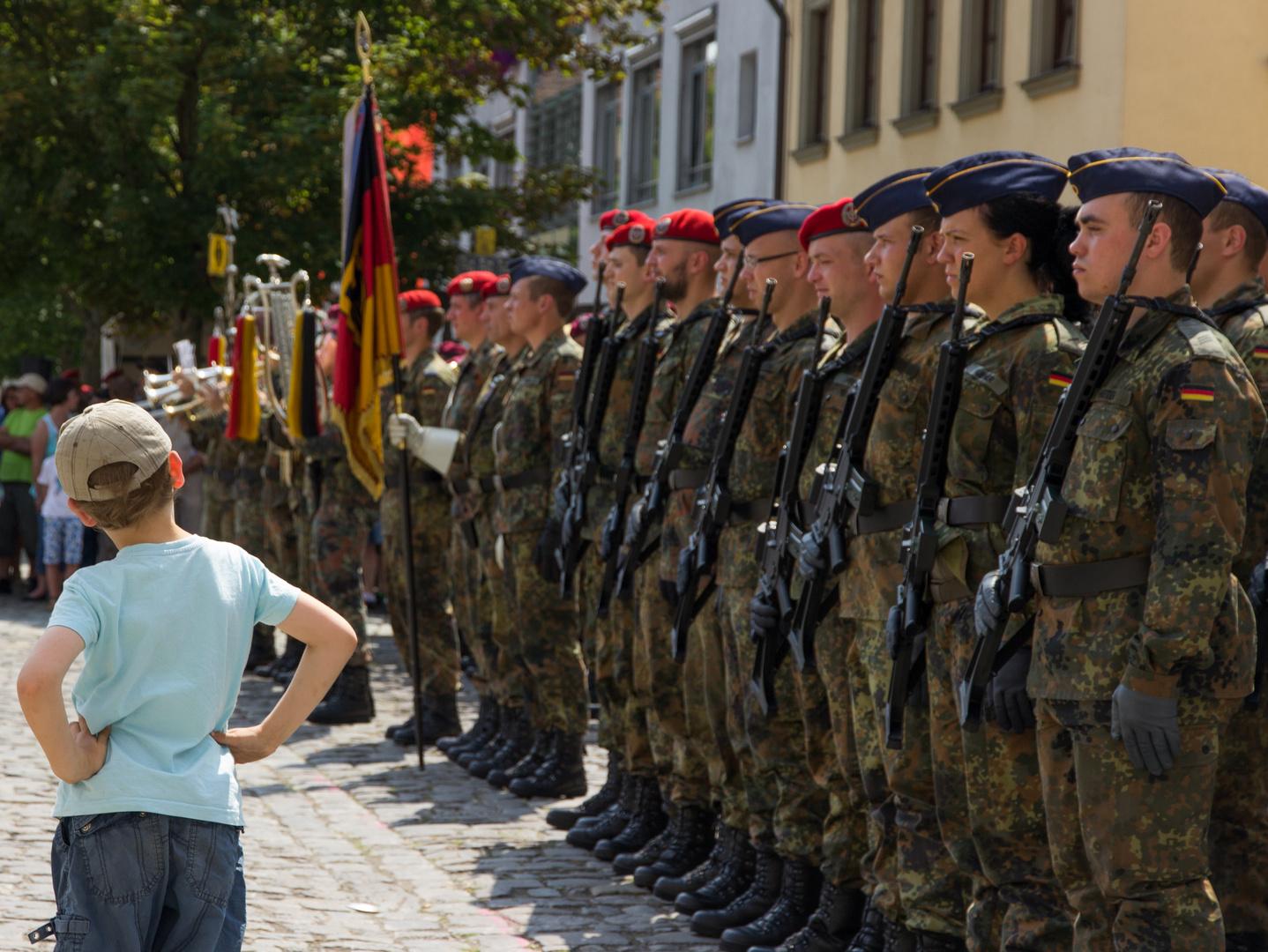 Kleiner Mann begutachtet Bundeswehr