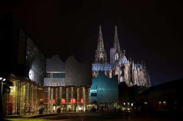Kölner Philharmonie mit Sicht auf den Dom bei Nacht