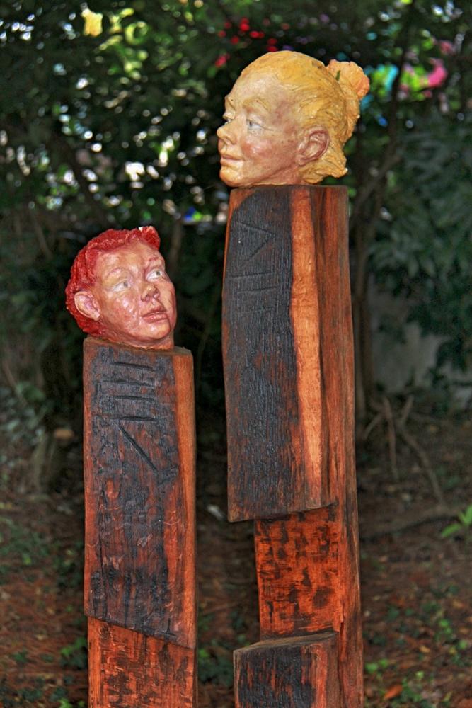 Köpfe auf Holzstelen
