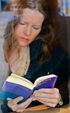 ... konzentriert Lesende hinter Scheibe