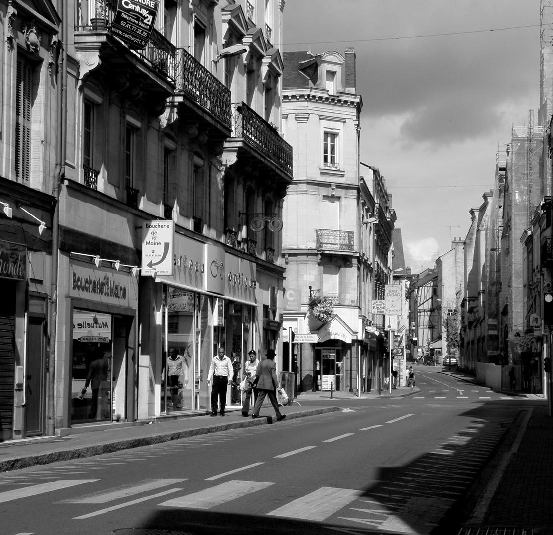 La rue où traverse l' homme à chapeau avec un journal.