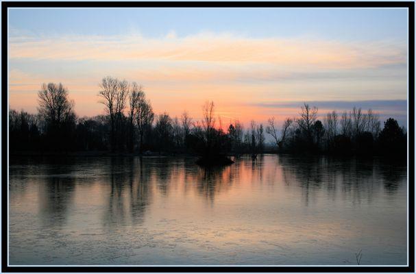 Lever de soleil sur un étang gelé